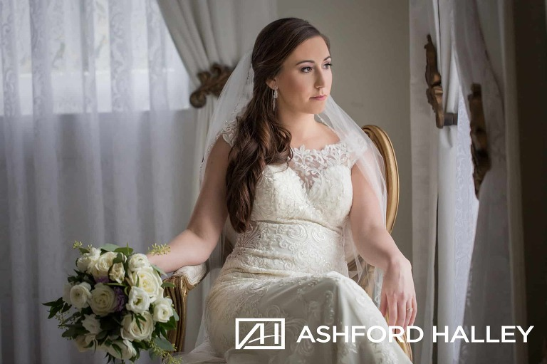 bride sitting in chair looking out window during bridal session