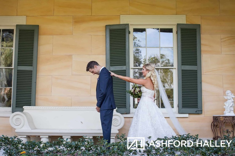 Bride tapping groom on shoulder during first look at Houmas House Plantation