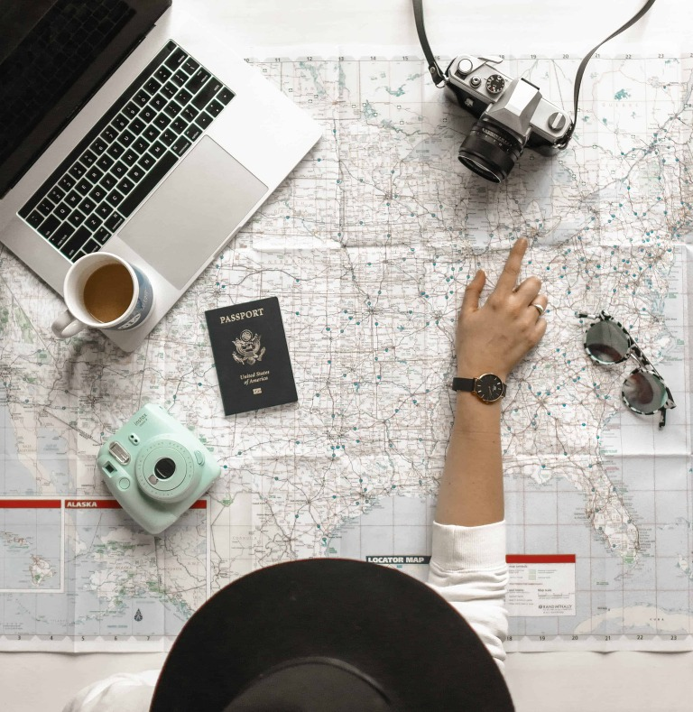 overhead view of hand pointing to honeymoon destinations on map with camera and laptop