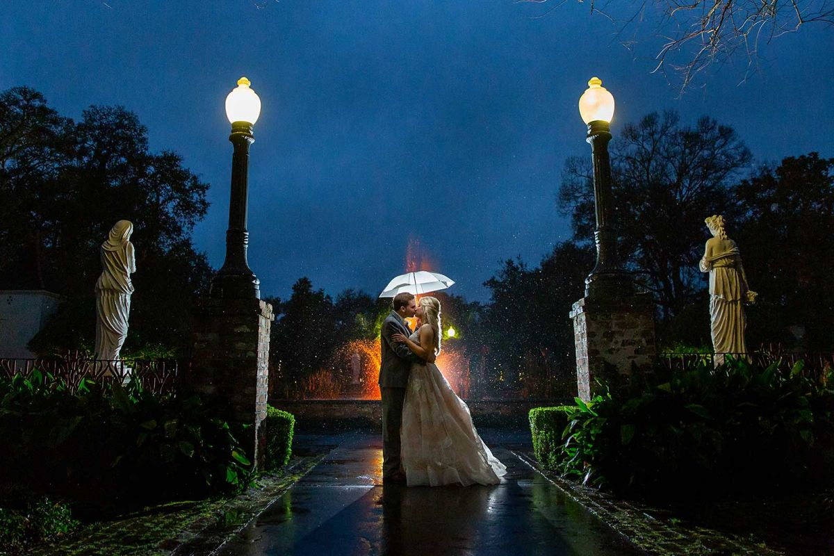 Bride and groom holding umbrella in front of fountain at Houmas House Plantation in Darrow, LA
