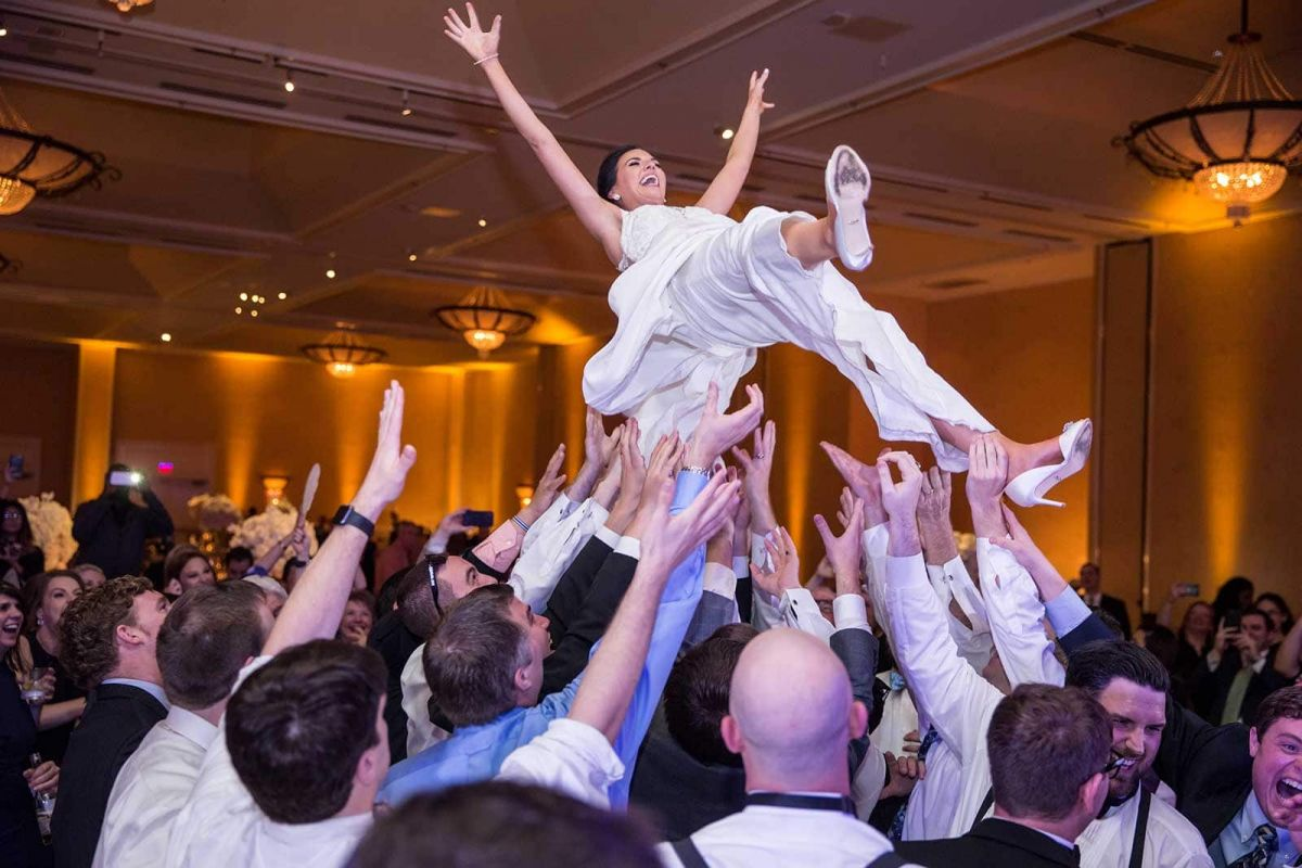 bride being thrown in the air at the reception